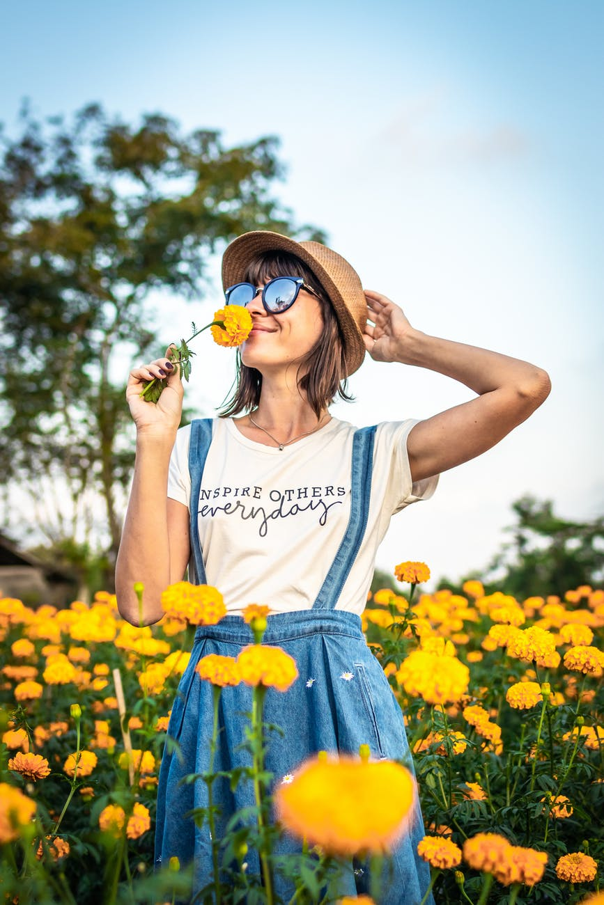 woman holding hat and smelling yellow flower