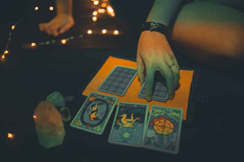crop female future teller with tarot cards on table