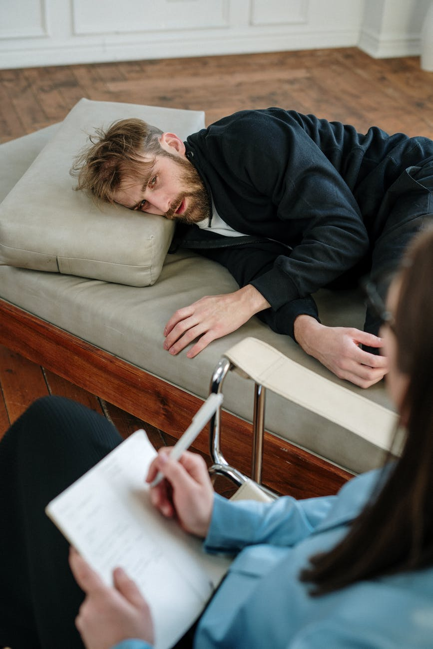 man in black jacket lying on couch