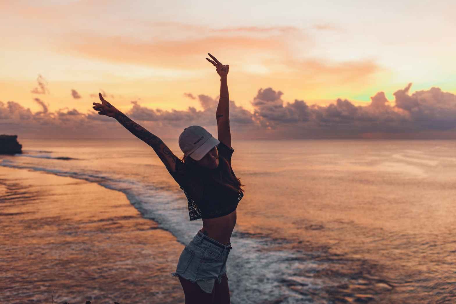 happy woman with raised arms against seascape