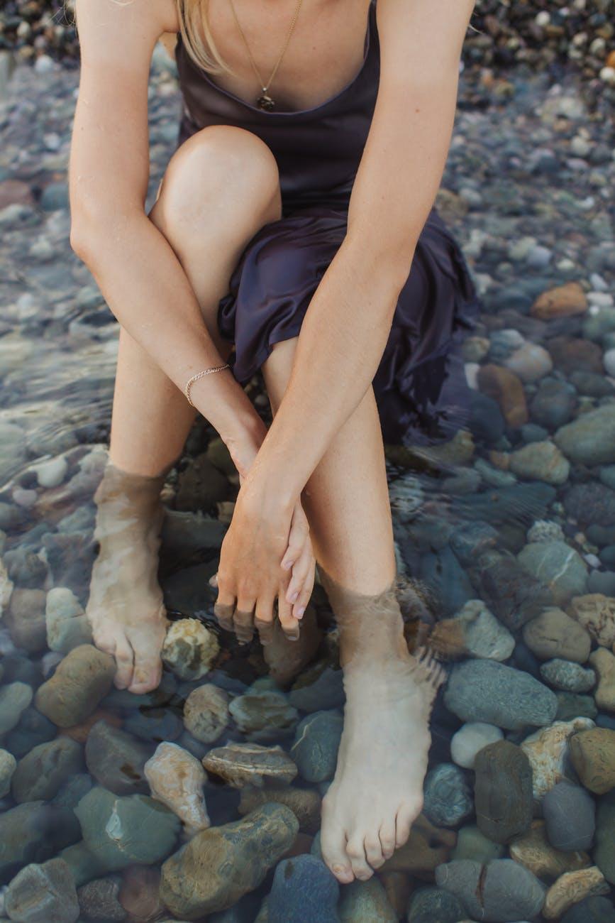 woman in blue sleeveless dress sitting on rocky shore