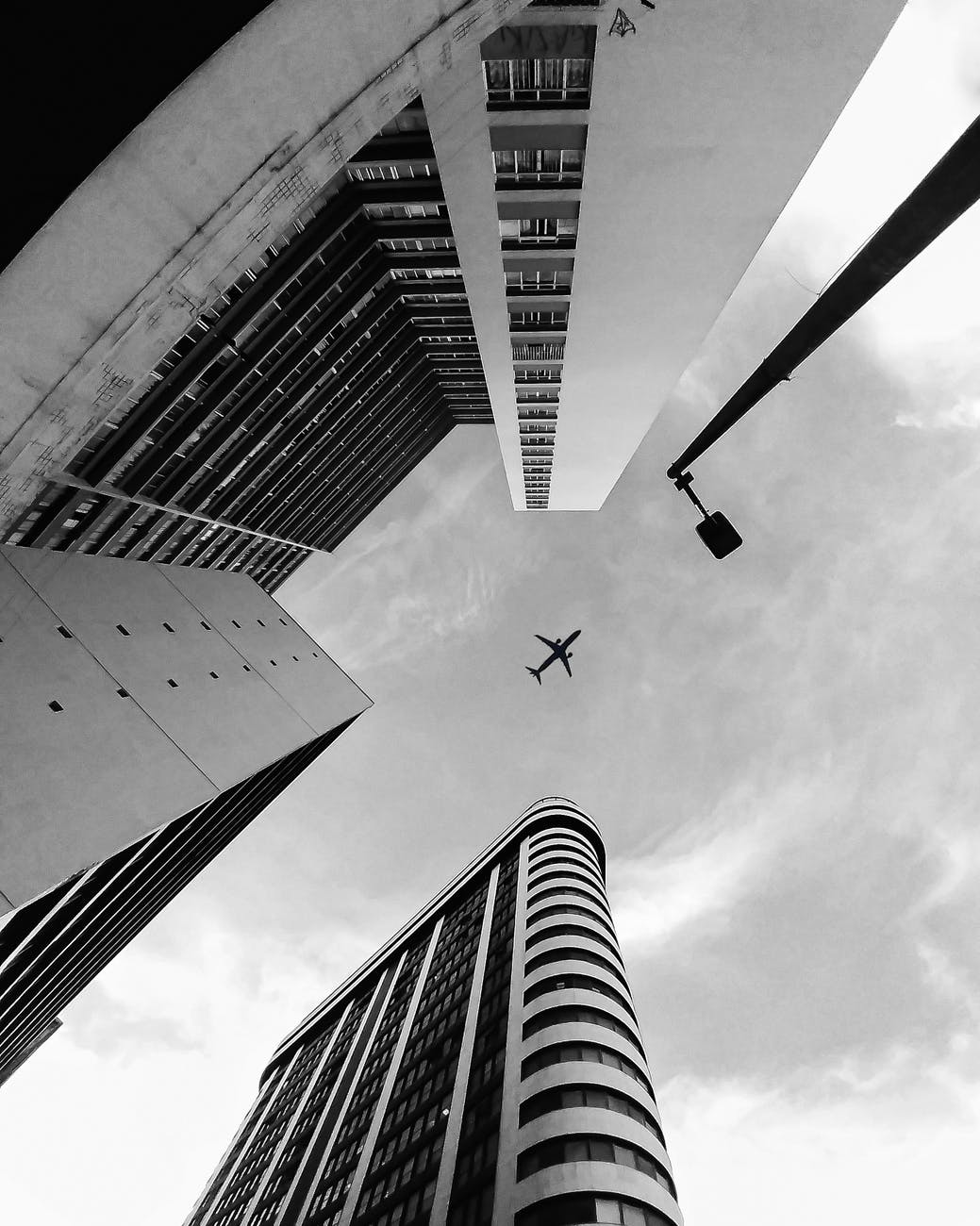 low angle photo of airplane flying over building