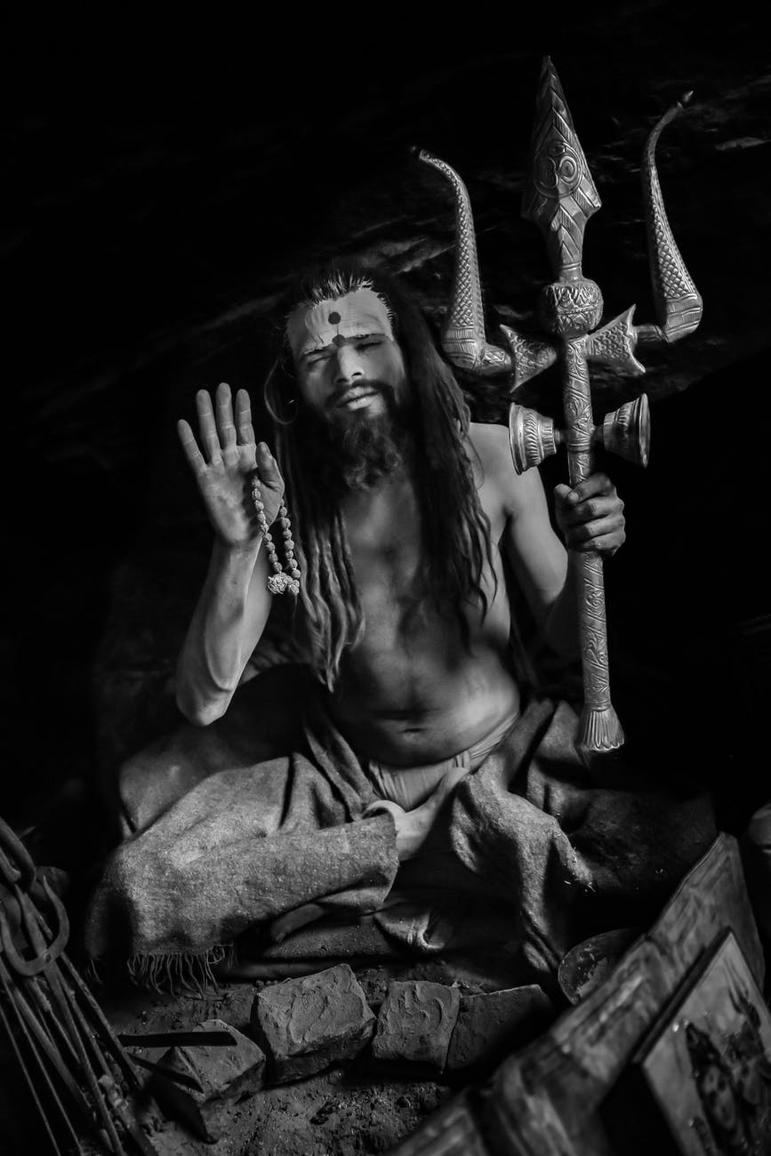 calm voodoo priest with trident sitting on ground